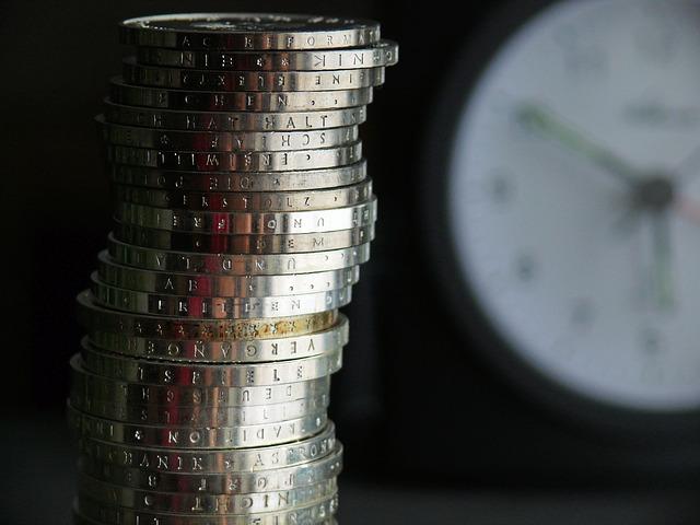 euro mince s hodinami v pozadí