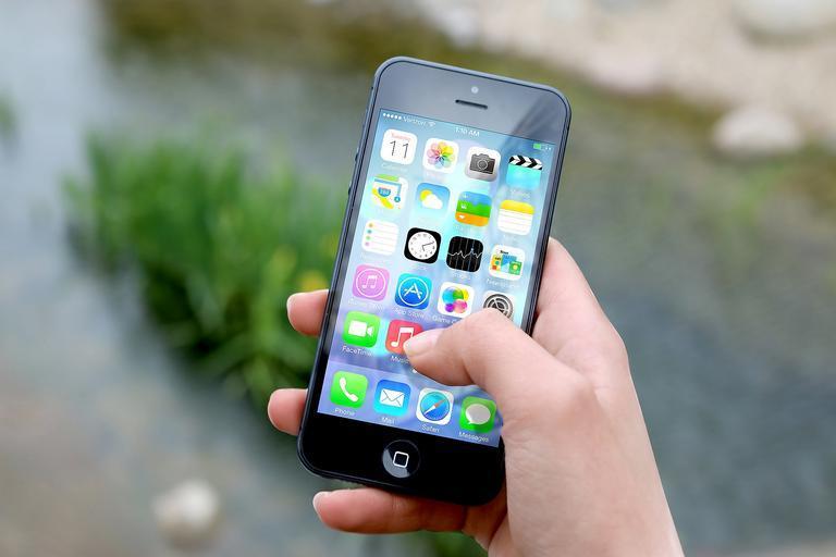 V ruce drží mobil s malými ikonami, v pozadí tráva a ulice