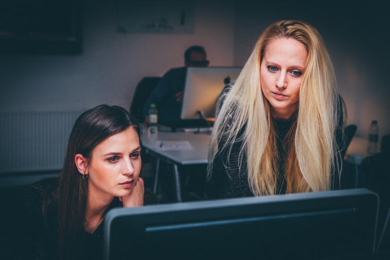 Dvě ženy sedící za počítačem, v popředí monitor, jedna blondýnka, druhá bruneta