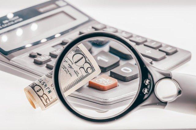kalkulačka a bankovka pod lupou